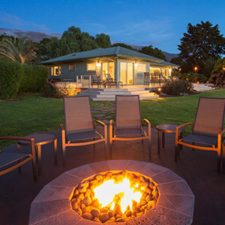 outdoor fire pit in a backyard surrounded by chairs