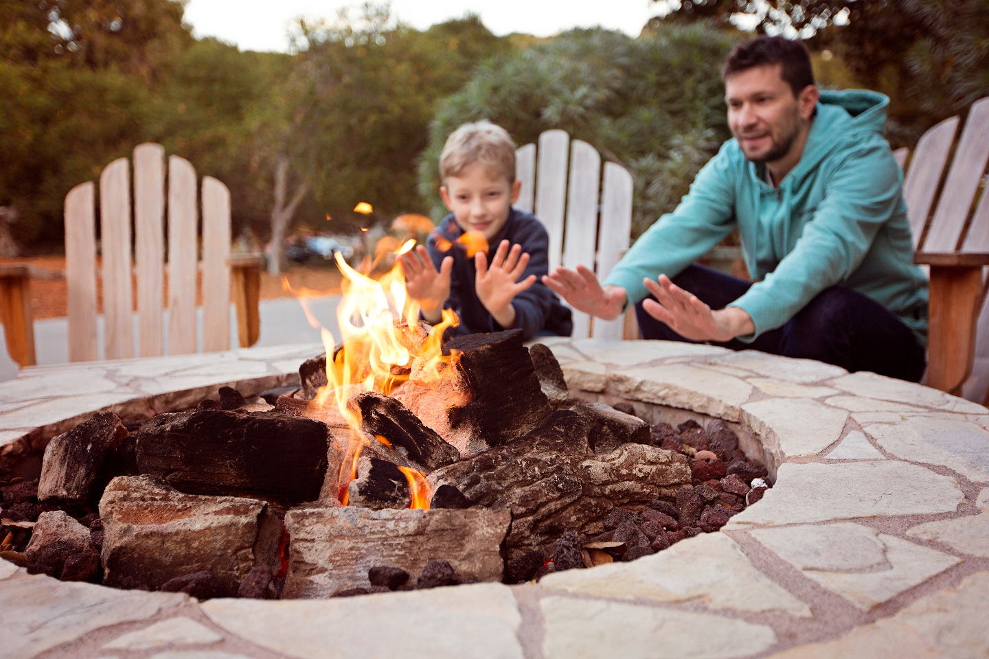 open outdoor fireplace with man and little boy warming their hands, sitting behind it.