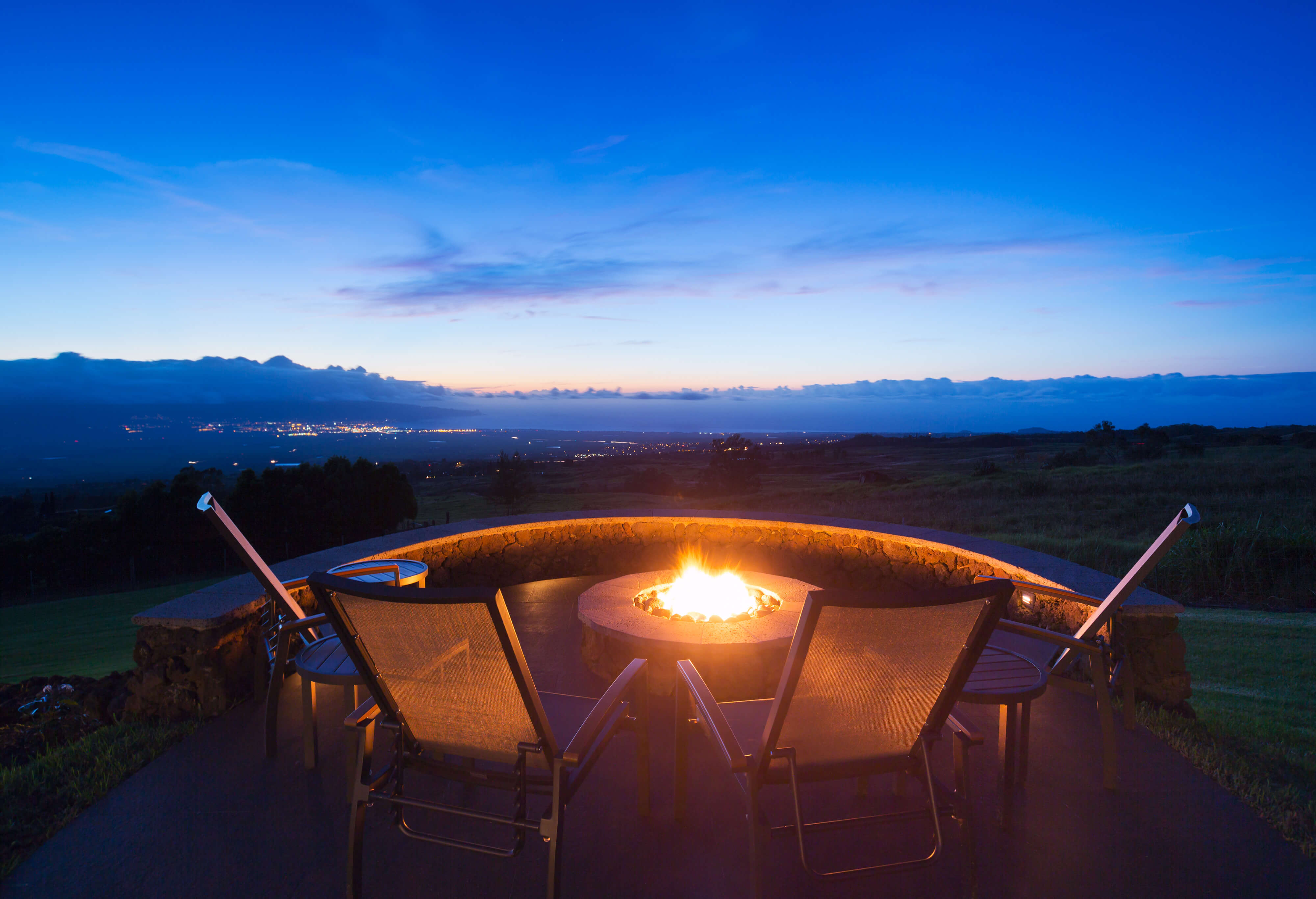 Fire pit surrounded by patio chairs facing a great view of sky and far off city lights