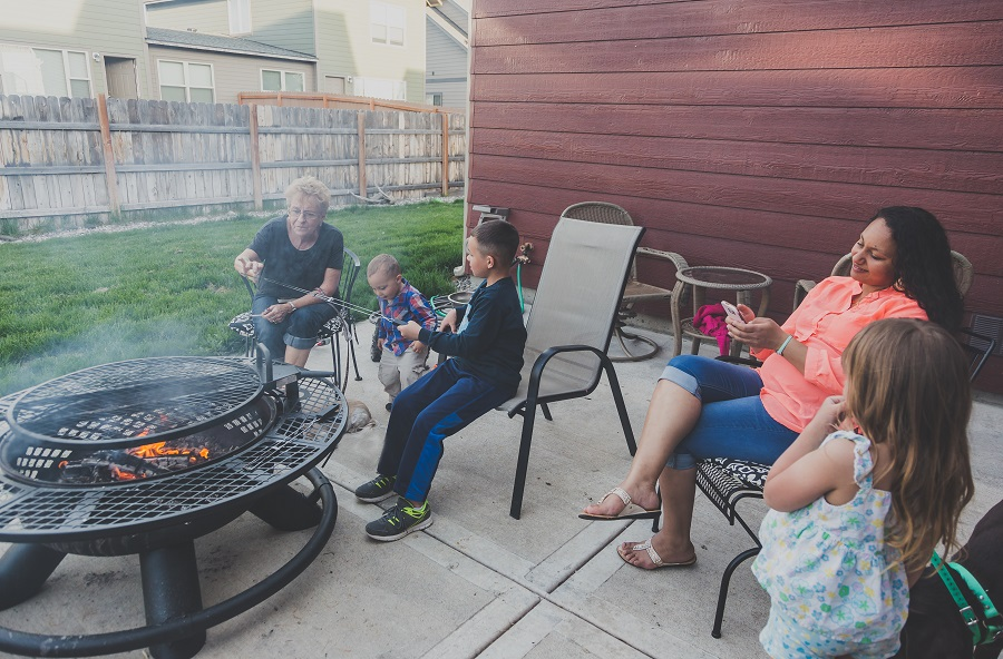 Family enjoying the outdoors cooking marshmallows over fire.