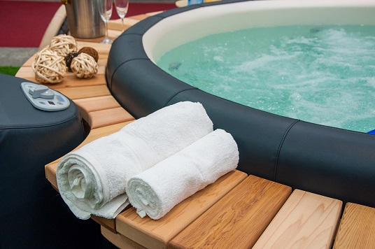 Detail view of luxury beautiful hot tub for relaxing, with decoration, towels, bottle of wine in nice interior.