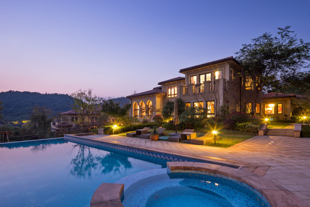 a beautiful pool in a home's backyard at sunset